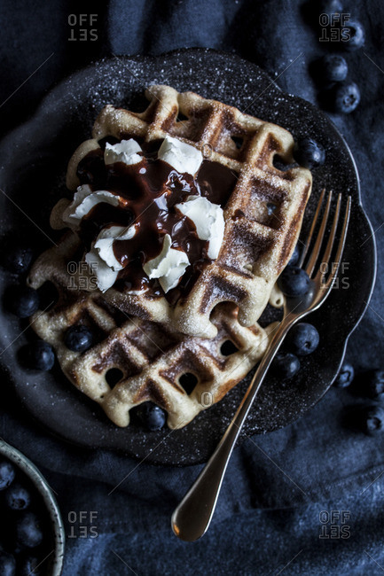 Waffles with whipped cream, blueberries, and chocolate sauce