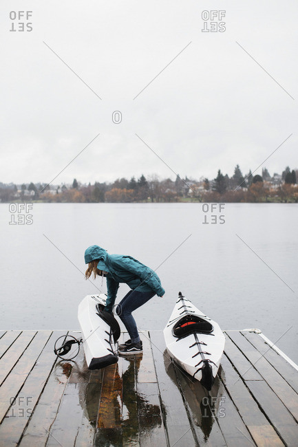 Woman with kayaks on dock