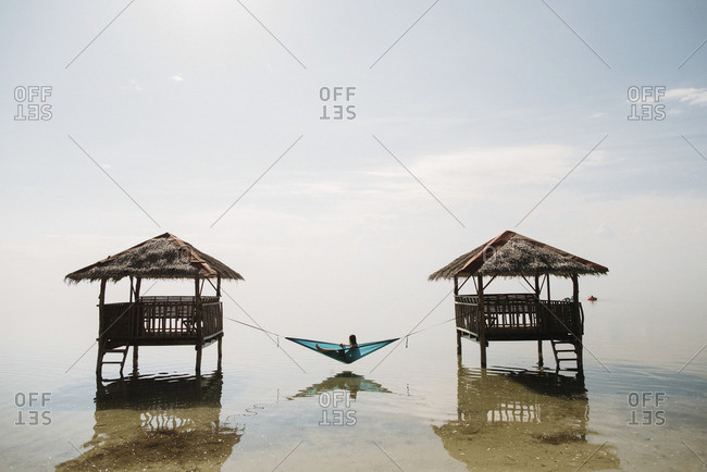 Woman on hammock over sea