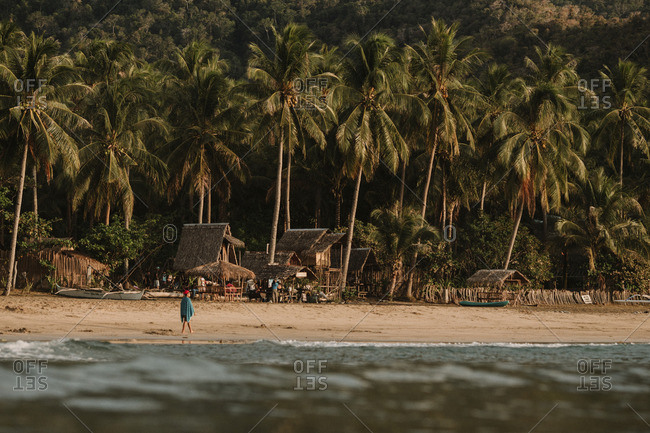 People by tropical beach cabanas