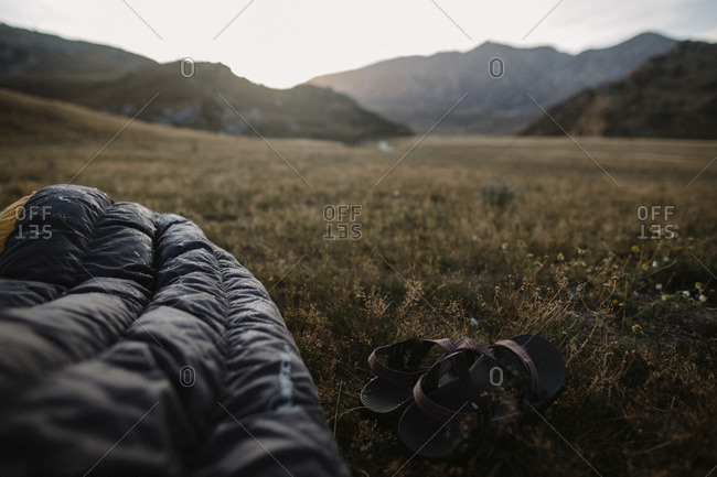 Sleeping bag and sandals in field
