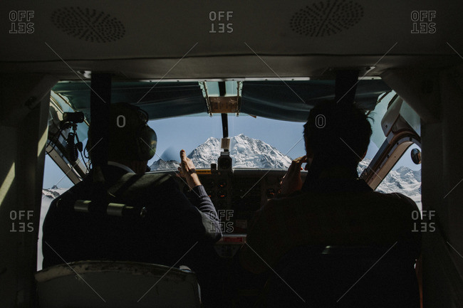 People in plane by mountains