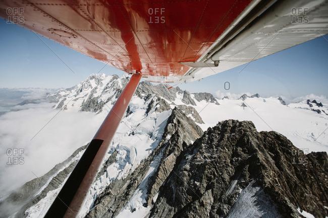 Plane wings over mountain range