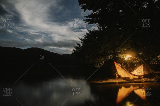 Person in hammock on lake shore