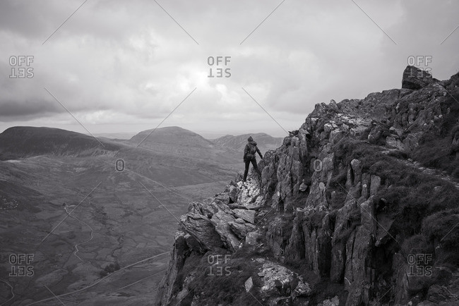 Woman standing on the edge of a mountain precipice