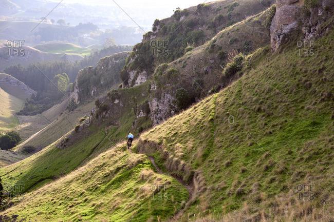 Person mountain biking down a remote mountain trail