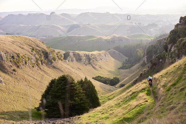 Person mountain biking down a remote mountain path