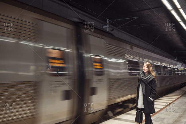 Train passing by woman standing at subway station