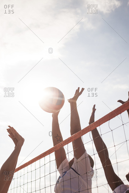 Low angle view of friends playing volleyball at beach against sky