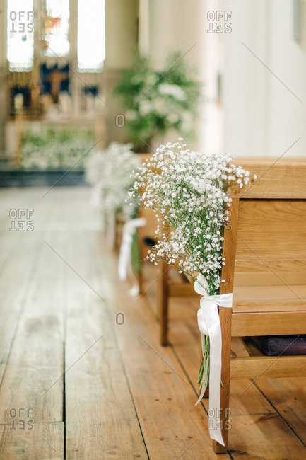 Baby\'s breath bouquets tied to the end of wood church pews in a wedding chapel
