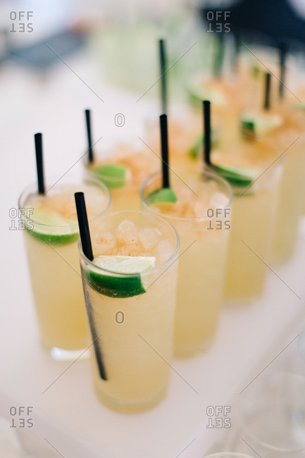 Close-up of alcoholic beverages with straws on a table at a wedding reception