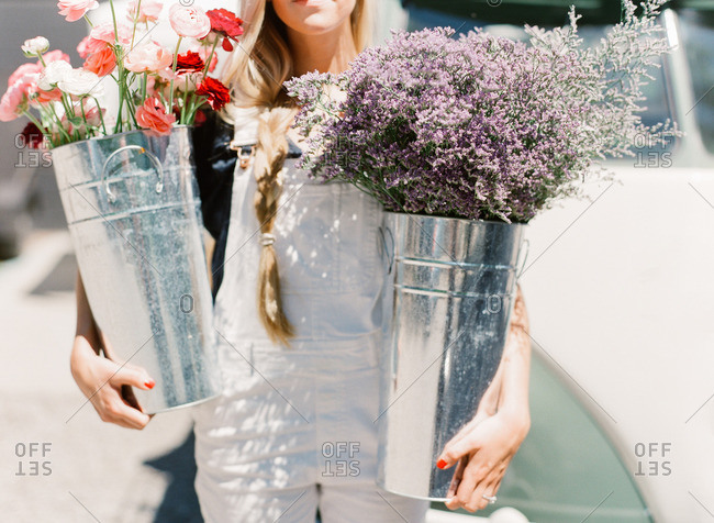 Woman carrying metal pails filled with fresh flowers