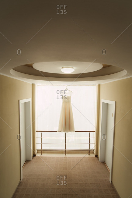 Wedding gown hanging in front of a window in a hotel hallway