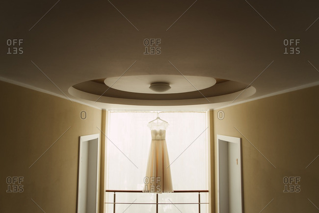 Wedding gown hanging in front of a window in a hotel
