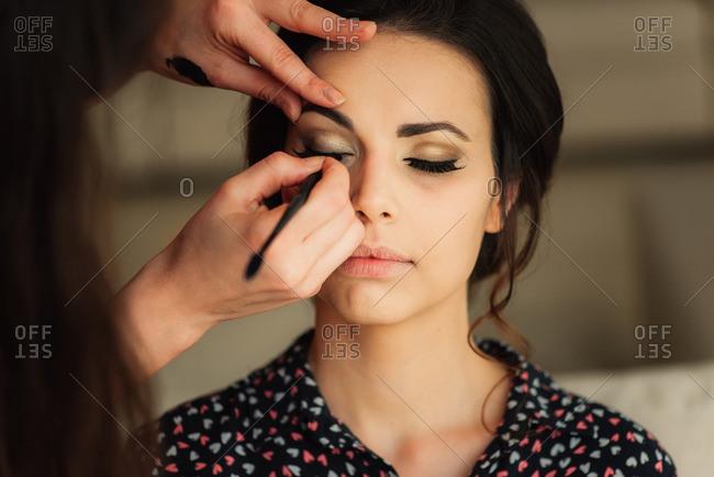 Woman applying bride's eye makeup