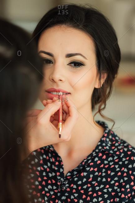 Woman applying bride's lipstick