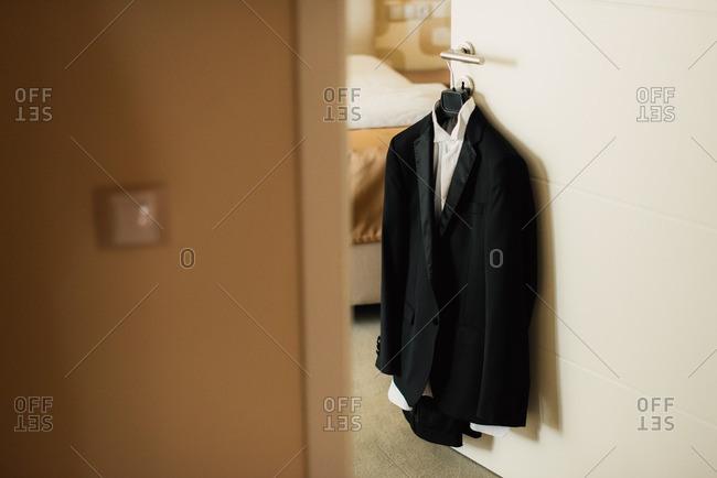 Groom's tuxedo hanging on a door