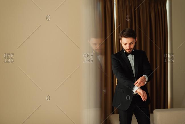 Groom adjusting sleeves on his tuxedo