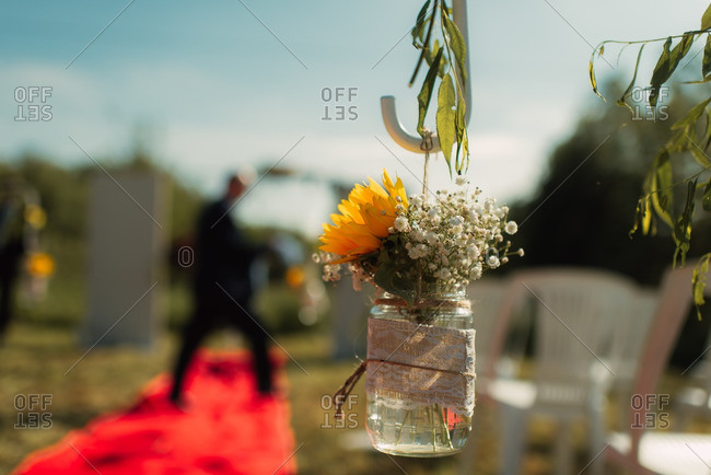 Hanging mason jar with flowers at a wedding ceremony