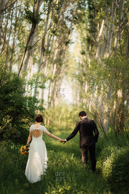 Bride and groom holding hands and walking in the woods