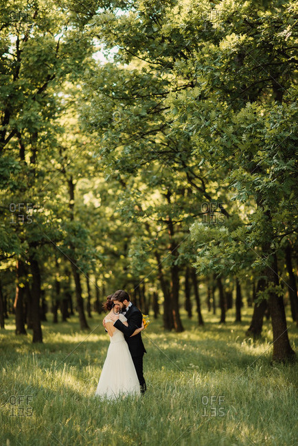 Newlyweds hugging in the woods