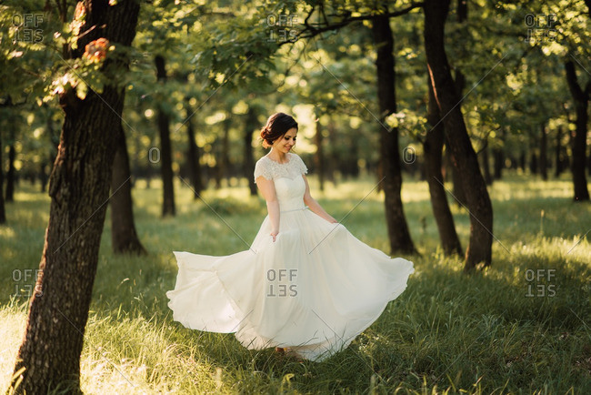 Bride dancing in her wedding gown in the woods