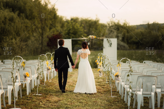 Husband and wife walking down aisle of countryside wedding ceremony