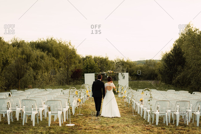 Bride and groom walking down aisle of countryside wedding ceremony