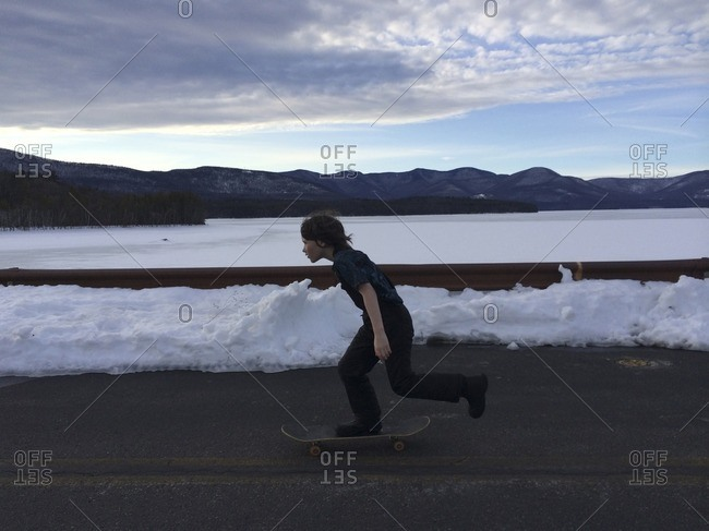 Full length side view of boy skateboarding on road by river during winter