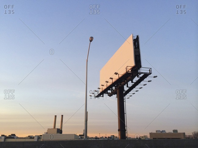 Low angle view of billboards and street light against clear blue sky