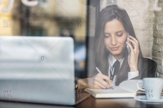 Businesswoman using smart phone while writing in diary at cafe