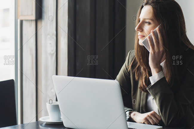 Businesswoman using smart phone looking away in cafe