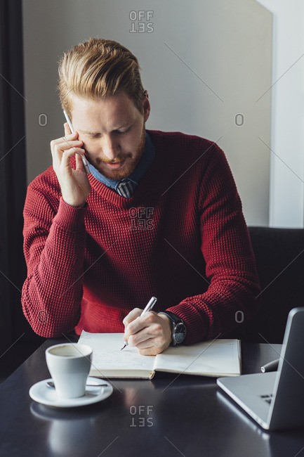 Businessman using mobile phone writing in diary at restaurant table