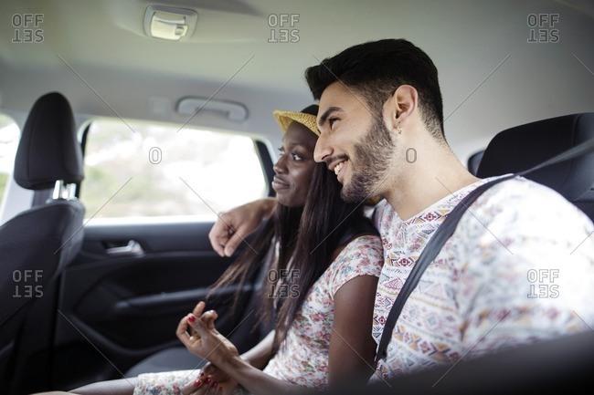 Happy multi-ethnic couple sitting in car