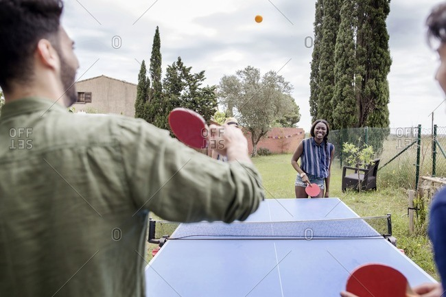 Multi-ethnic friends playing table tennis at yard