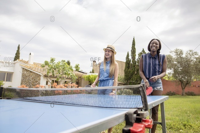 Happy women playing table tennis at yard