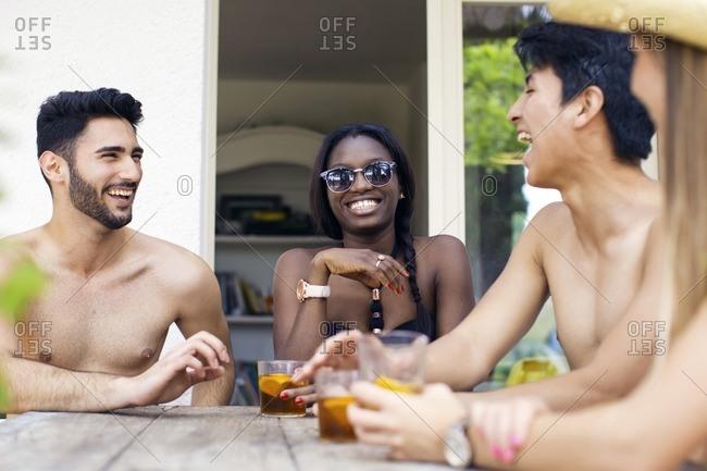 Happy friends in swimwear having drinks at outdoor table