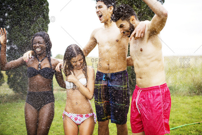 Cheerful friends in swimwear enjoying water spray at yard