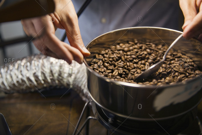 Midsection of man roasting coffee beans in machinery at cafe