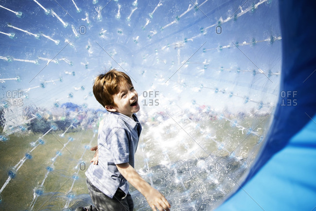 Cheerful boy in an inflatable ball