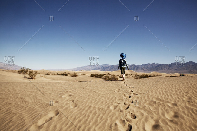 Rear view of boy walking at desert against clear blue sky