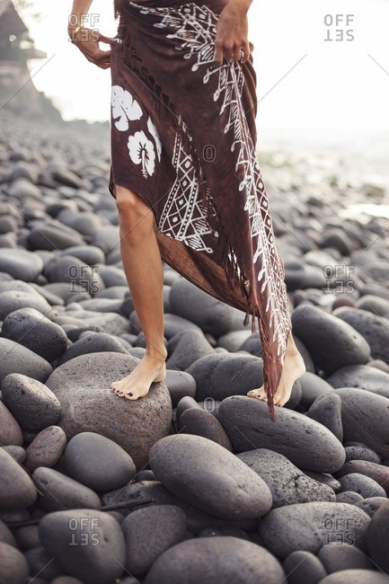 Low section of woman in sarong walking on rocks at beach