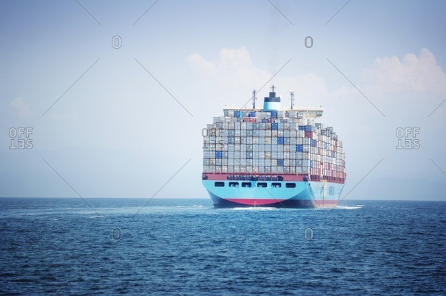 Container ship loaded with cargo containers sailing on sea against sky