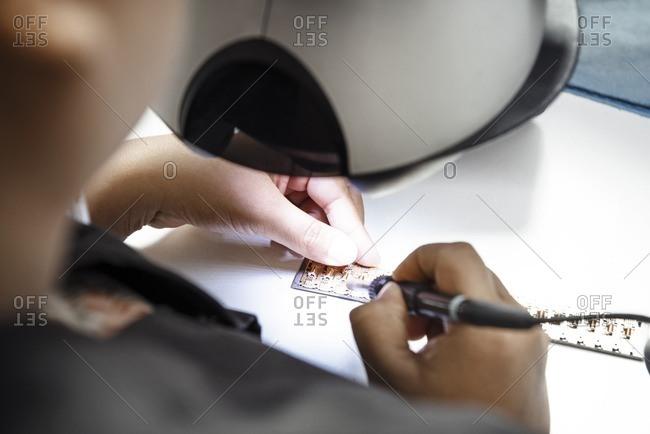 Technician making circuit board in industry
