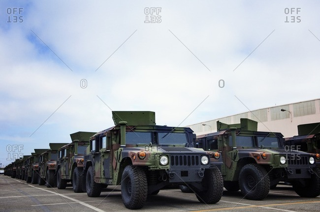 Military vehicles parked at industry against cloudy sky