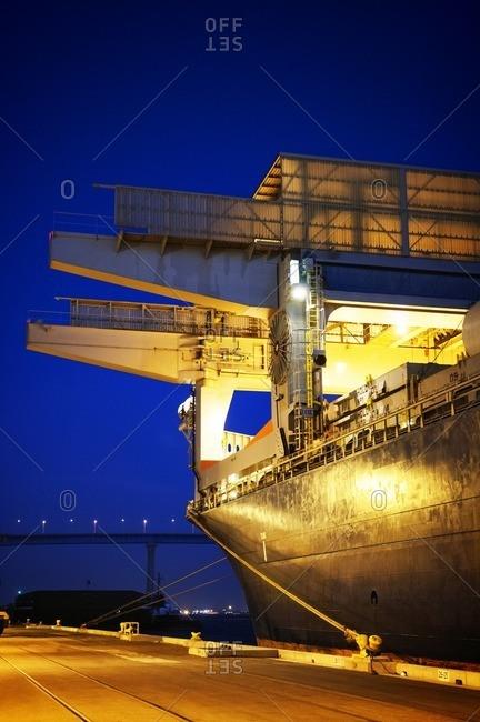 Illuminated container ship moored at harbor at dusk