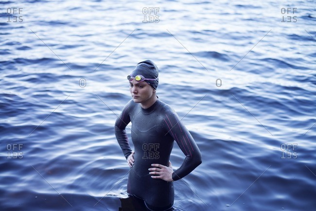 High angle view of thoughtful swimmer standing with hand on hip in lake