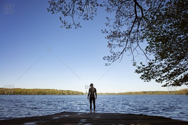 Rear view of female swimmer standing on boardwalk by lake against clear blue sky