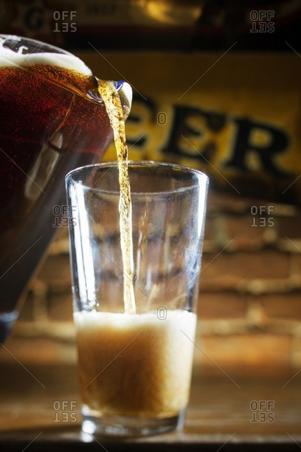 Beer being poured from pitcher in glass