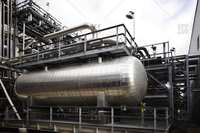 Metallic pipelines at power station against sky